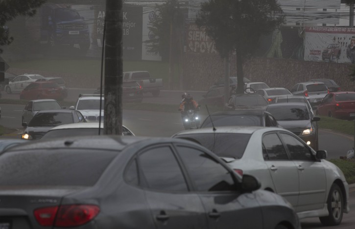 Drivers make their way through a light rain of volcanic ash, as the Volcan de Fuego erupts, in Guatemala City, Sunday, June 3, 2018. Volcan del Fuego is one of the most active volcanoes in Central America. (AP Photo/Luis Soto)