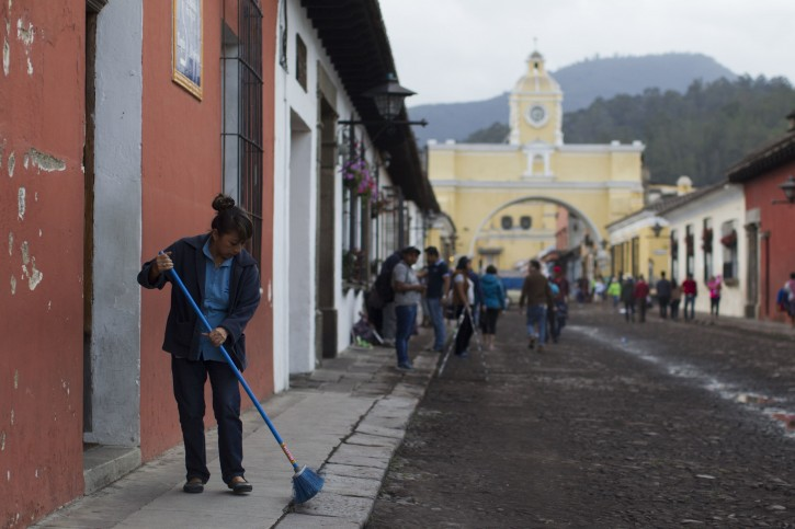 A woman sweeps volcanic ash brought by the Volcan del Fuego, from the sidewalk in Antigua Guatemala, Sunday, June 3, 2018. Volcan del Fuego is one of the most active volcanoes in Central America. (AP Photo/Luis Soto)
