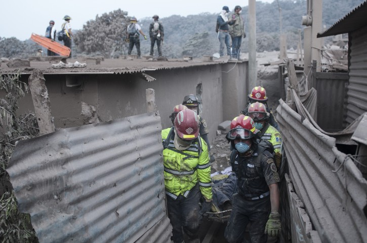 "Firefighters remove a body recovered near the Volcan de Fuego, or ""Volcano of Fire,"" in Escuintla, Guatemala, Monday, June 4, 2018. Rescuers have found the bodies of several more victims of an eruption at Guatemala's Volcano of Fire, and emergency workers have pulled some people still alive from ash drifts and mud flows. (AP Photo/Oliver de Ros)"