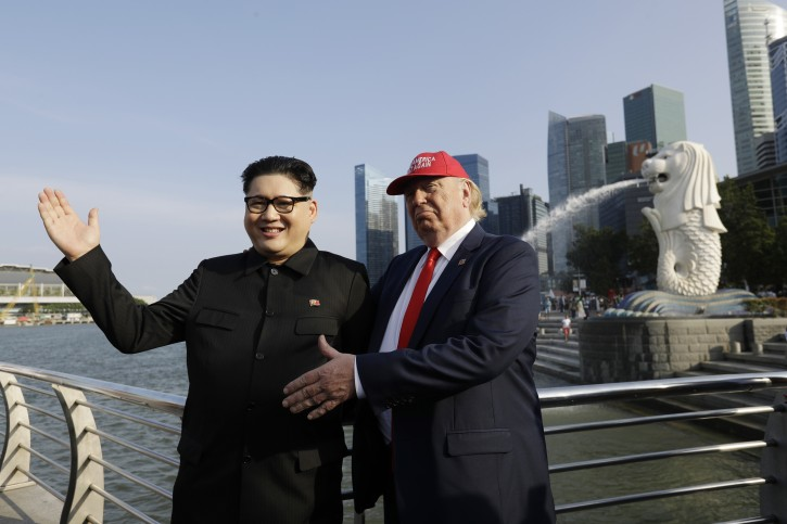 Kim Jong Un and Donald Trump impersonators, Howard X, left, and Dennis Alan, right, pose for photographs at the Merlion Park, a popular tourist destination in Singapore, on Friday, June 8, 2018. Kim Jong Un lookalike who uses the name Howard X said he was detained and questioned upon his arrival in Singapore on Friday, days before a summit between the North Korean leader and President Donald Trump. (AP Photo/Wong Maye-E)