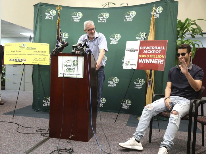 Tayeb Souami, left, of Little Ferry, introduces his son Inel during a press conference announcing Souami as the $351.3 million Powerball winner, Friday, June 8, 2018, in Trenton, N.J. (Chris Pedota/The Record via AP)