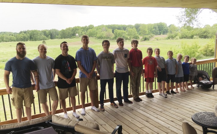 In a photo from May 30, 2018, the 14 brothers of the Schwandt family pose for a photo at their farm in Lakeview, Mich. From left are Tyler, Zach, Drew, Brandon, Tommy, Vinny, Calvin, Gabe, Wesley, Charlie, Luke, Tucker, Francisco and Finley. The boys range in age from 2 months to 25 years. They have no sisters. (AP Photo/Mike Householder)