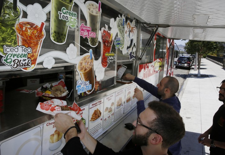 In this Friday, June 8, 2018, photo the Japanese food truck, Okamoto Kitchen serves customers in Beverly Hills, Calif.  (AP Photo/Damian Dovarganes)