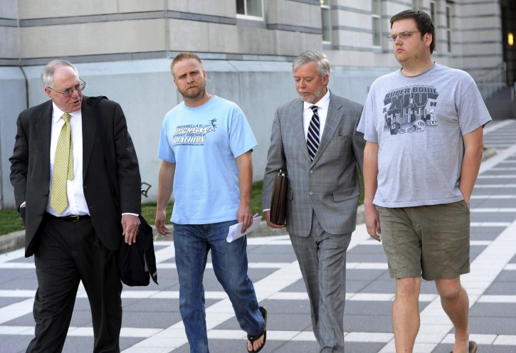 David Nicoll, 39 of Mountain Lakes (blue shirt), president of Biodiagnostic laboratory Services, LLC, and employee and brother Scott Nicoll, 32 of Wayne (gray shirt), leaves Federal Court in Newark Tuesday afternoon with representatives after being arrested for his involvement in an alleged scheme in which BLS made tens of millions of dollars by bribing doctors to refer business and order unnecessary patient tests in Newark. (Tyson Trish/Northjersey.com via AP)