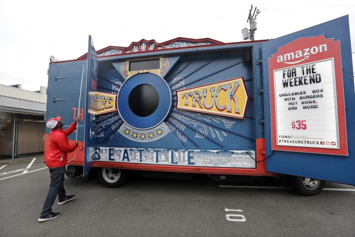In this May 24, 2018, photo Amazon worker Khayyam Kain begins to open an Amazon Treasure Truck at a parking lot in Seattle. (AP Photo/Elaine Thompson)