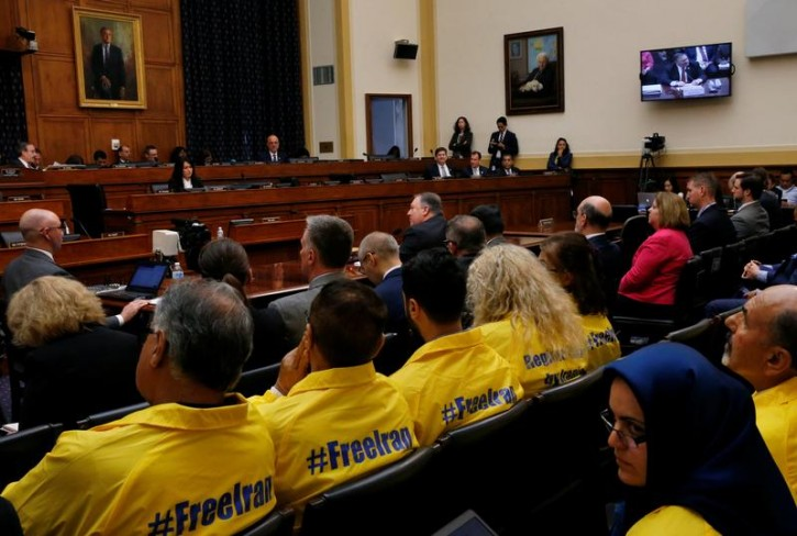"""U.S. Secretary of State Mike Pompeo testifies at a hearing of the U.S. House Foreign Affairs Committee as people sit in the audience behind him wearing """"#FreeIran"""" jackets on Capitol Hill in Washington, U.S., May 23, 2018. REUTERS/Leah Millis"""