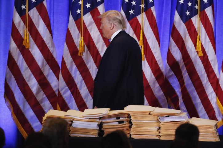 FILE - U.S. President-elect Donald Trump walks past a pile of papers during a news conference in the lobby of Trump Tower in Manhattan, New York City, U.S., January 11, 2017. REUTERS/Lucas Jackson