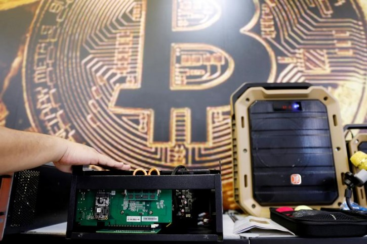 A cryptocurrency mining computer is seen in front of bitcoin logo during the annual Computex computer exhibition in Taipei, Taiwan June 5, 2018. REUTERS/Tyrone Siu