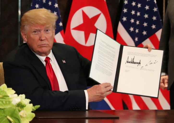 U.S. President Donald Trump shows the document, that he and North Korea's leader Kim Jong Un signed acknowledging the progress of the talks and pledge to keep momentum going, after their summit at the Capella Hotel on Sentosa island in Singapore June 12, 2018.   REUTERS/Jonathan Ernst