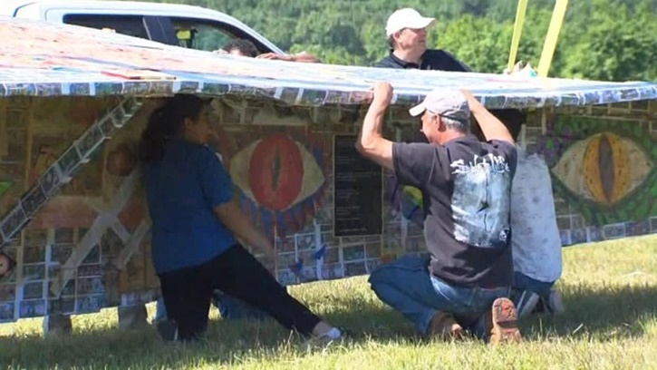 The 64-foot paper airplane is covered in pieces of art. (WBZ-TV)