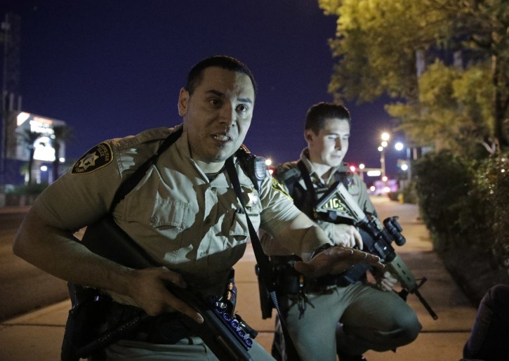 FILE - In this Oct. 1, 2017, file photo, police officers advise people to take cover near the scene of a shooting near the Mandalay Bay resort and casino on the Las Vegas Strip in Las Vegas. A veteran police officer's self-described freeze in a Las Vegas hotel hallway while a gunman fired on an outdoor concert crowd is prompting a review of whether lives could have been saved if officers had acted faster to stop the mass shooting. (AP Photo/John Locher, File)