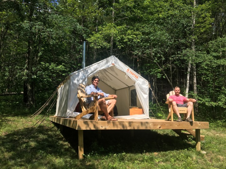 In this Friday, June 29, 2018, photo, Michael D'Agostino, left, sits with David Derstine at his Tentrr campsite on a 200-acre organic farm in Berlin, N.Y. D'Agostino, CEO of Tentrr, says it's like Airbnb or Uber for the great outdoors, providing a platform for landowners to earn some cash by sharing secluded and scenic sites for camping. (AP Photo/Mary Esch)