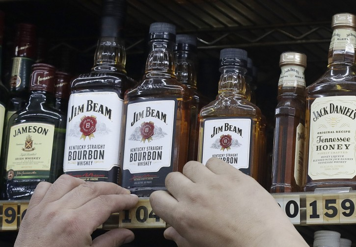 This July 9, 2018, photo shows a man adjusting prices under bottles of Jim Beam bourbon whiskey displayed at Rossi's Deli in San Francisco. AP