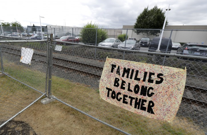 "A sign that reads ""Families belong Together"" hangs on a fence outside the Northwest Detention Center in Tacoma, Wash., Tuesday, July 10, 2018. (AP Photo/Ted S. Warren)"