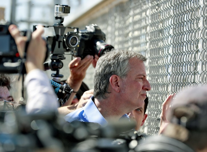 New York City Mayor Bill de Blasio looks through a closed gate at the Port of Entry facility, Thursday, June 21, 2018, in Fabens, TX., where tent shelters are being used to house separated family members. (AP Photo/Matt York)