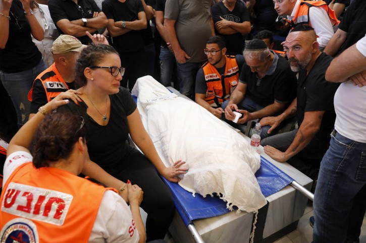 Wife (L) of Israeli Yotam Ovadia and his father (2-R) mourn next to his body during his funeral at the Givat Shaul cemetery in Jerusalem, Israel, 27 July 2018. EPA
