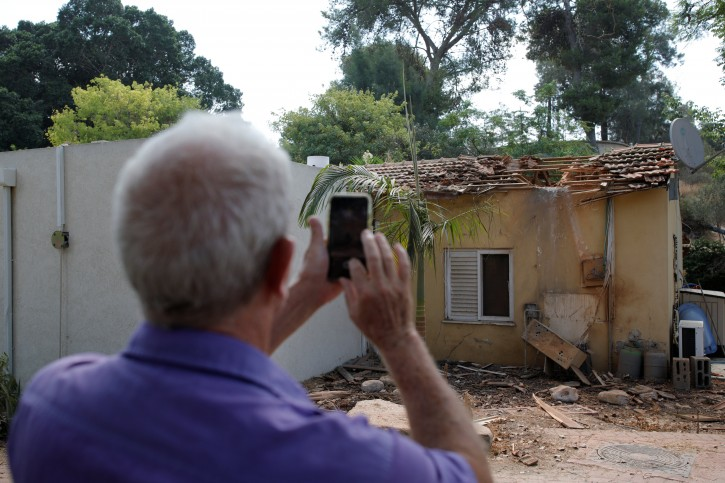 An Israeli man takes pictures with his phone next to the scene where a rocket exploded in the southern Kibbutz of Yad Mordechai, Israel August 9, 2018. REUTERS/Amir Cohen