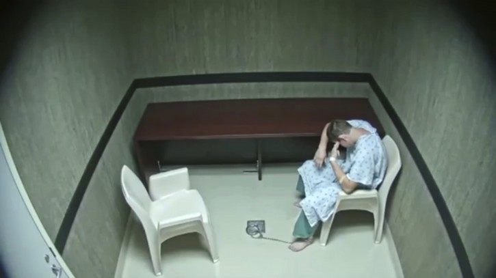 In this image made from video provided on Wednesday, Aug. 8, 2018, by the Broward County Sheriff's Office, Nikolas Cruz points his fingers to his temple at an interrogation room, while officers are out of the room, in Fort Lauderdale, Fla. (Broward County Sheriff's Office via AP)