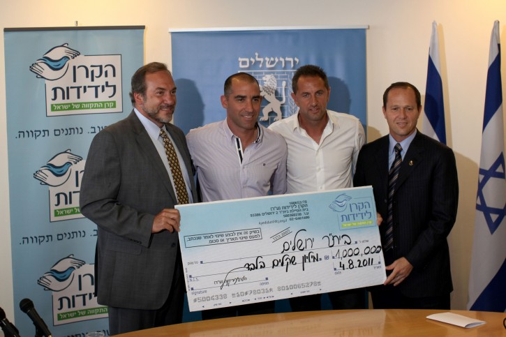 FILE - Rabbi Yechiel Eckstein,(L) founder and president of the International Fellowship of Christians and Jews (IFCJ) giving a donation check of one million nis to the chairman of Beitar Jerusalem, Itzik Kornfein and the head coach David Amsalem with the help and support of Jerusalem mayor Nir Barkat (R) at Barkat's offices in Jerusalem on Aug 04, 2011. Photo by Kobi Gideon/Flash90.