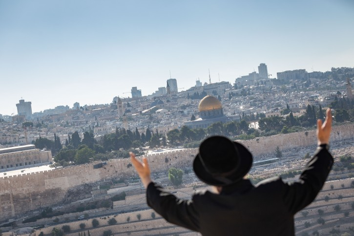 An Ultra Orthodox Jewish man prays as he faces the view of the Temple Mount and the Dome of the Rock from the Mount of Olives in Jerusalem, on August 9, 2018. Photo by Flash90