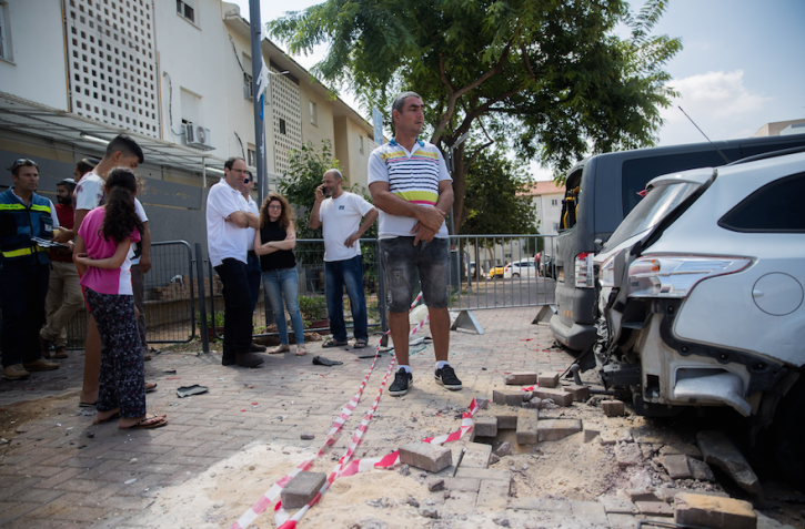 Sderot residents view the site where a mortar shell from Gaza hit the southern Israeli city near the border, Aug. 9, 2018. (Yonatan Sindel/Flash90)