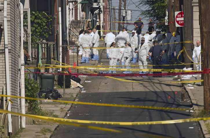 Police join members of the ATF and the FBI as they investigate North Hall Street in Allentown, Pa., Sunday, Sept. 30, 2018, after a fiery car explosion rocked the neighborhood on Saturday. Police confirmed at least one fatality and at least 50 investigators remain on the scene scouring for evidence. (Harry Fisher/The Morning Call via AP)