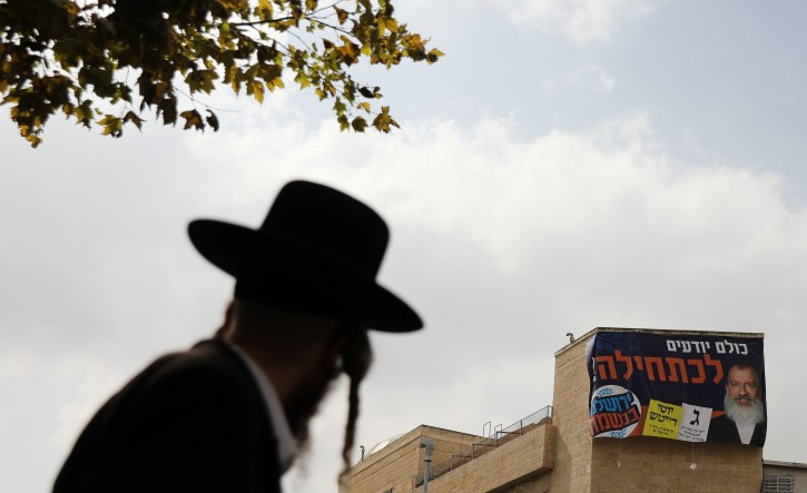 A campaign poster depicting ultra-Orthodox Jewish candidate in Jerusalem's mayoral election Yossi Daitsh is seen on a building as an ultra-Orthodox man looks on, in Jerusalem October 18, 2018. REUTERS/Ammar Awad