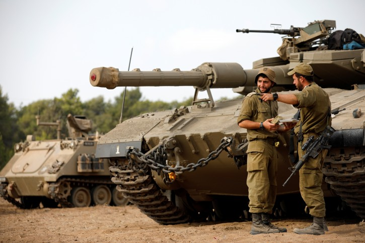 Israeli soldiers speak next to a tank as military armoured vehicles gather in an open area near Israel's border with the Gaza Strip October 18, 2018. REUTERS/Amir Cohen