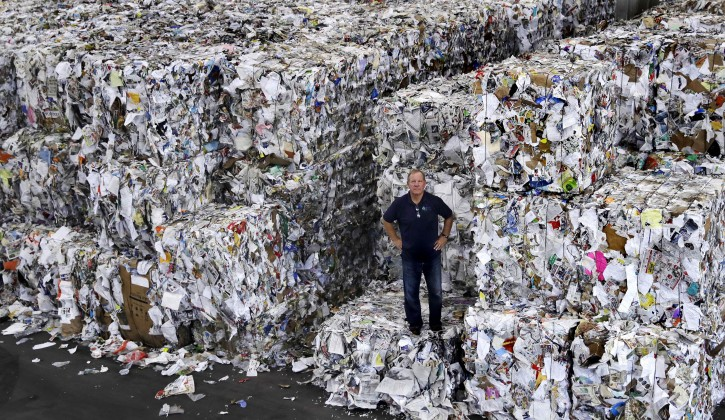 In this Thursday, Sept. 6, 2018, photo, Ben Harvey, an owner at EL Harvey & Sons, a waste and recycling company, poses on bundles of residential mixed fiber, comprised of a variety of paper and cardboard, in Westborough, Mass. The company is currently stacking and holding onto about 2,500 tons of the material, which is awaiting a destination where a recycler will process the bundles. Recycling programs across the United States are shutting down or scaling back because of a global market crisis blamed on contamination at the curbside bin. (AP Photo/Charles Krupa)