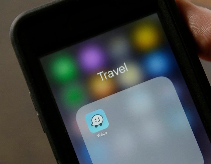 FILE - In this March 27, 2017, file photo, the Waze application is displayed on a smartphone in San Francisco. On Wednesday, Oct. 10, 2018, Google announced it will begin offering its pay-to-carpool service throughout the U.S. in an effort to reduce the commute-time congestion that its popular Waze navigation app is designed to avoid. (AP Photo/Eric Risberg, File)