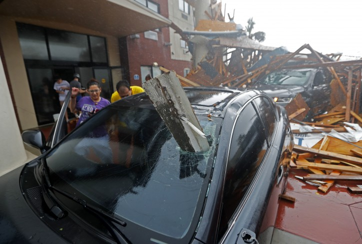 A woman checks on her vehicle as the eye of  Hurricane Michael passes through, after the hotel canopy had just collapsed, in Panama City Beach, Fla., Wednesday, Oct. 10, 2018. (AP Photo/Gerald Herbert)