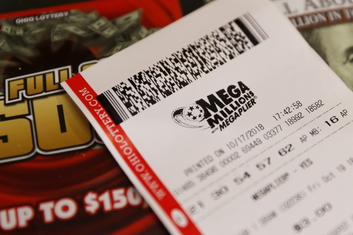 A Mega Millions lottery ticket rests on the shop counter at the Street Corner Market, Wednesday, Oct. 17, 2018, in Cincinnati. AP Photo/John Minchillo)