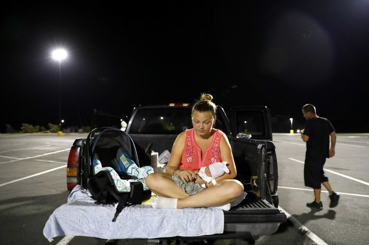 FILE - In this Monday, Oct. 15, 2018 file photo, Lorrainda Smith sits with her 2-day-old son, Luke, as she contemplates with her husband, Wilmer Capps, right, sleeping in their truck in a parking lot after their home was damaged from Hurricane Michael and they were told a nearby shelter was closed, in Panama City, Fla. AP