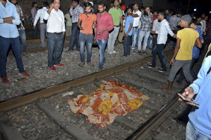 The body of a victim of a train accident lies covered in cloth on a railway track in Amritsar, India, Friday, Oct. 19, 2018. A speeding train ran over a crowd watching fireworks during a religious festival in northern India on Friday, killing at least 50 people, a Congress party leader said. (AP Photo/Prabhjot Gill)