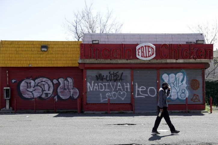 """In this April 26, 2018, photo a man walks by a closed restaurant along Bergen Street in a so-called """"opportunity zone"""" in Newark, N.J. The Trump administration on Friday, Oct. 19, proposed rules for investors in a new program that it says could have a big impact on economically depressed areas around the country. About 8,700 of the opportunity zones have been set up in all 50 states and to lure investors and developers with tax breaks. (AP Photo/Julio Cortez)"""