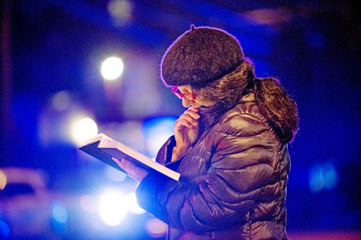 Nancy Clark of Squirrel Hill, reads from the Tehillim, as police lights flash and rain soaks the pages, yards away from Tree of Life Congregation, on Saturday, Oct. 27, 2018, in the Squirrel Hill section of Pittsburgh. AP