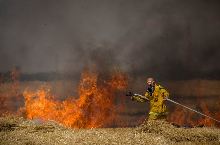 Israeli firefighters extinguish a fire in a wheat field caused from kites flown by Palestinian protesters, near the border with the Gaza Strip, May 30, 2018. (Yonatan Sindel/Flash90)