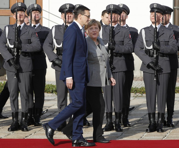 Polish Prime Minister Mateusz Morawiecki, front left, welcomes German Chancellor Angela Merkel, front right, ahead of intergovernmental consultations in Warsaw, Poland, Friday Nov. 2, 2018. Merkel is visiting Warsaw amid calls by Polish officials that Germany pay Poland billions of dollars for damage inflicted by the Nazis during World War II. (AP Photo/Czarek Sokolowski)