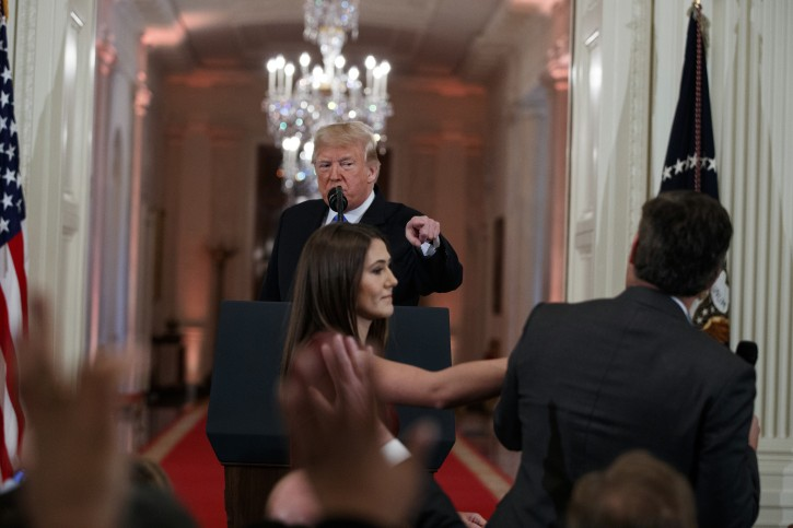 President Donald Trump looks on as a White House aide attempts to take away a microphone from CNN journalist Jim Acosta during a news conference in the East Room of the White House, Wednesday, Nov. 7, 2018, in Washington. (AP Photo/Evan Vucci)