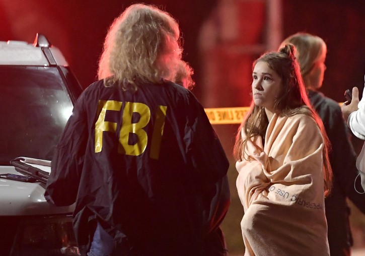 """An FBI agent talks to a potential witness as they stand near the scene Thursday, Nov. 8, 2018, in Thousand Oaks, Calif. where a gunman opened fire Wednesday inside a country dance bar crowded with hundreds of people on """"college night,"""" wounding 11 people including a deputy who rushed to the scene. Ventura County sheriff's spokesman says gunman is dead inside the bar. (AP Photo/Mark J. Terrill)"""