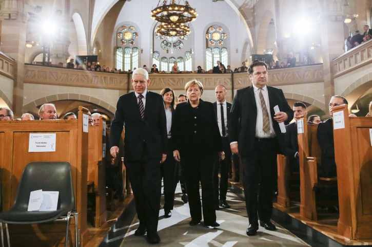 Flanked by the President of the Central Council of Jews in Germany Josef Schuster, left, and Gideon Joffe, right, head of the Jewish community in Berlin. German Chancellor Angela Merkel, center, arrive at the synagogue Rykestrasse at the district Prenzlauer Berg in Berlin, Friday, Nov. 9, 2018 for an event commemorating the Night of Broken Glass 1938, in which Nazis burned and vandalized synagogues and Jewish businesses across the country and killing over 400 people. (AP Photo/Markus Schreiber)