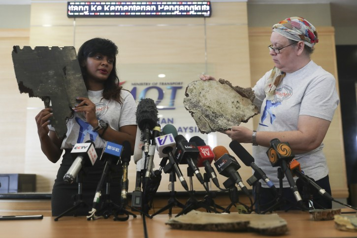 Grace Subathirai Nathan, (L) daughter of missing Malaysia Airlines flight MH370 passenger Anne Daisy and  also MH370 #SearchOn Campaign leader and Jacquita Gonzales (R) widow of missing MH370 in-flight supervisor, Patrick Francis Gomez, shows a part of the debris believed to belong to MH370 during press conference at ministry of transport headquarters in Putrajaya, Malaysia, 30 November 2018.  EPA