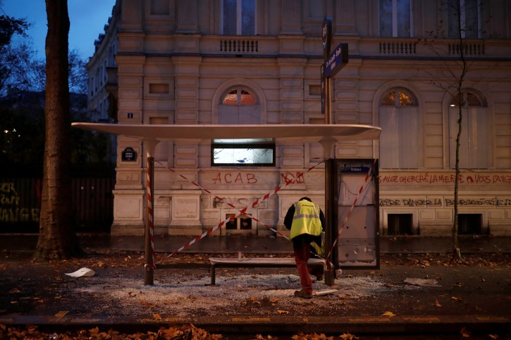 An employee inspects a vandalized bus stop the morning after clashes with protesters wearing yellow vests, a symbol of a French drivers' protest against higher diesel fuel taxes, in Paris, France, December 2, 2018.  REUTERS/Benoit Tessier