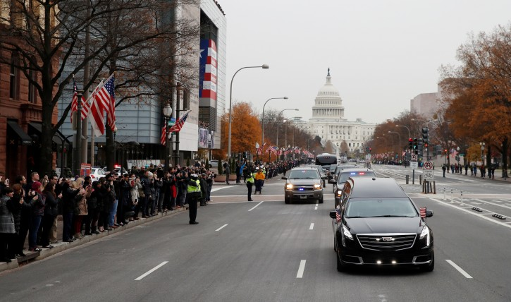People line Pennsylvania Ave. as the hearse passes by carrying the flag-draped casket of former President George H.W. Bush as it drives away from the Capitol heading to a State Funeral at the National Cathedral, Wednesday, Dec. 5, 2018, in Washington.  Alex Brandon/Pool via REUTERS