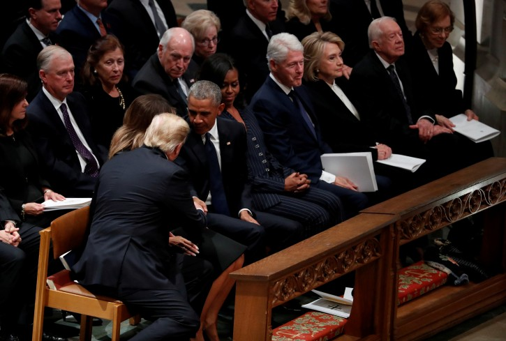 U.S. President Donald Trump reaches over to shake hands with former President Barack Obama as he takes his seat in the first row along with former first lady Michelle Obama, former President Bill Clinton and former first lady Hillary Clinton, former President Jimmy Carter and first lady Rosalynn Carter prior to the state funeral for former U.S. President George H.W. Bush at the Washington National Cathedral in Washington, U.S., December 5, 2018. REUTERS/Kevin Lamarque