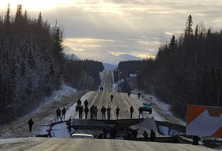 In this photo provided by Jonathan M. Lettow, people walk along Vine Road after an earthquake, Friday, Nov. 30, 2018, in Wasilla, Alaska. Back-to-back earthquakes measuring 7.0 and 5.7 rocked buildings and shattered roads Friday morning in Anchorage, sending people running into the streets and briefly triggering a warning to residents in Kodiak to flee to higher ground for fear of a tsunami. (Jonathan M. Lettow via AP)