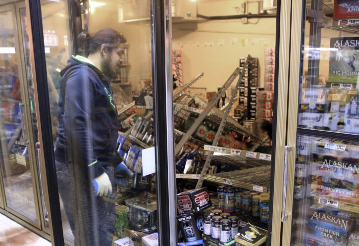 """Aisoli Lealasola prepares to clean up fallen cases of beer in a cooler at a liquor store, Value Liquor, after an earthquake on Friday, Nov. 30, 2018, in Anchorage, Alaska. Owner Mary Funner says beer, wine and other bottled alcohol was strewn throughout store aisles after the quake. She considered closing Friday until customers began lining up. They were allowed to come in in small groups. """"We're still in business, but we're only open only a little bit at a time,"""" she said. (AP Photo/Dan Joling)"""