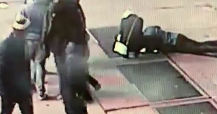 In this Nov. 30, 2018 image taken from surveillance video provided by the New York City Police Department, a man tries to see the engagement ring that he dropped down a utility grate on New York's Times Square. AP