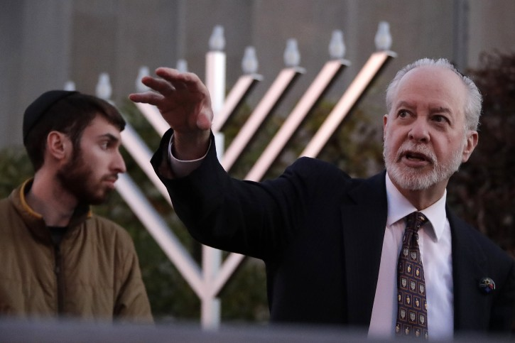 Rabbi Jeffrey Myers, right and his son Aaron oversee the installation of a menorah outside the Tree of Life Synagogue before holding a celebration on the first night of Hanukkah, Sunday, Dec. 2, 2018 in the Squirrel Hill neighborhood of Pittsburgh. A gunman shot and killed 11 people while they worshipped Saturday, Oct. 27, 2018 at the temple. (AP Photo/Gene J. Puskar)