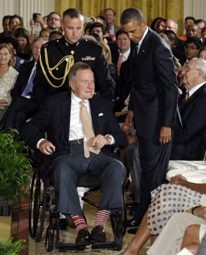 Former President George H.W. Bush, in a pair of red and white socks, is wheeled off of the stage to sit next to President Barack Obama after presenting the 5,000th Daily Point of Light Award at the White House in Washington on July 15, 2013. (AP Photo/Susan Walsh, File)